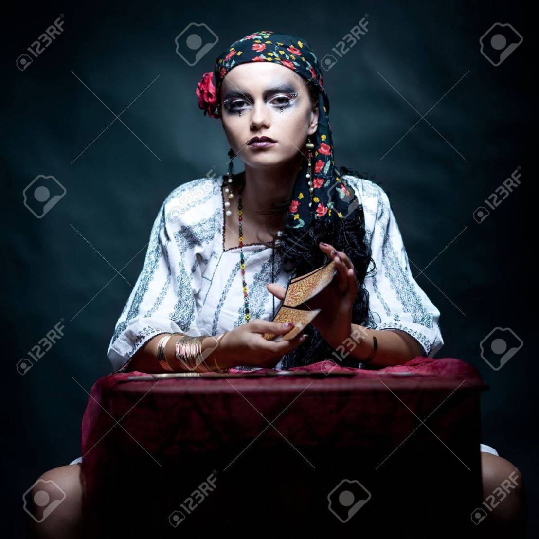 8894649-a-portrait-of-a-gypsy-fortune-teller-sitting-at-a-table-and-mixing-the-tarot-cards-that-she-holds-in